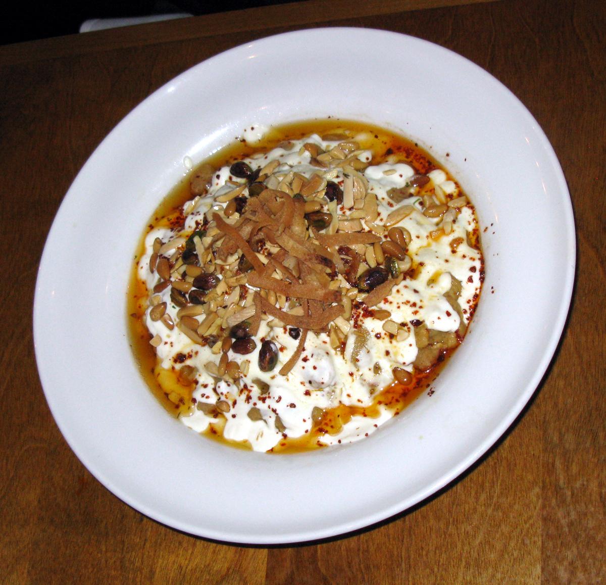 Fatteh hummus (فتة حمص بالطحينه)—chickpeas layered with pine nuts, tahini-yogurt sauce, and toasted pita bread