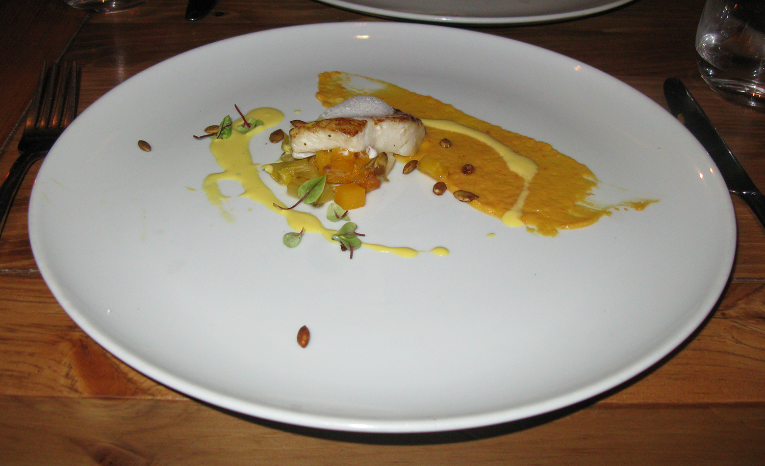 Pan-seared and steamed whiting fish with leeks, pumpkin seeds, saffron foam, saffron reduction, and butternut squash prepared two ways